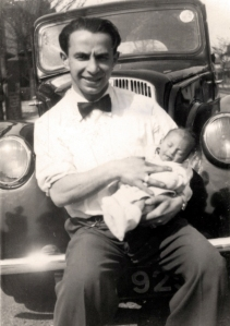 Holding his first son, 1955